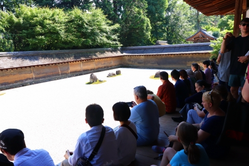 Conference attendees (and others) meditate and relax before the rock garden at Ryoanji Zen Buddhist Temple. Photo credit: Yu Kominami